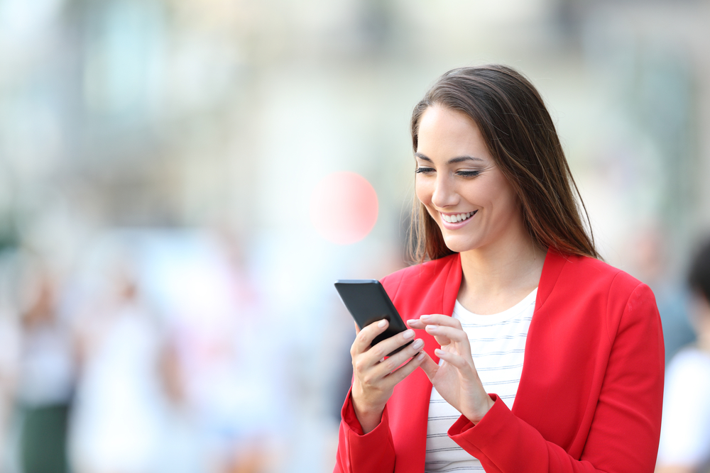 A woman looks happy to be browsing on her phone while outside.