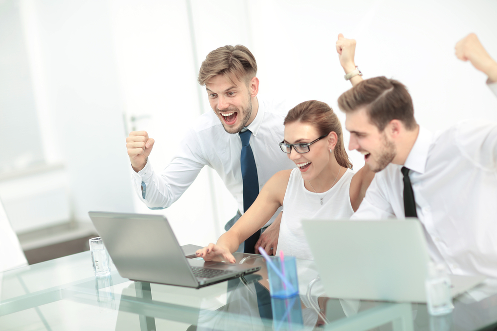 Business team getting excited about marketing results on their laptop