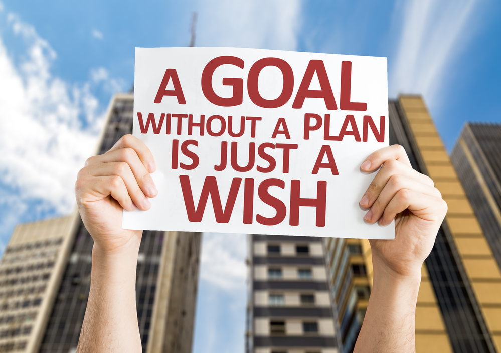 A sign being held stating a goal without a plan is just a wish